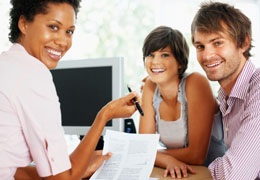 Three friends smiling holding some tax information