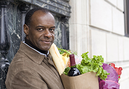 African American man carrying a bag of groceries in kitchen